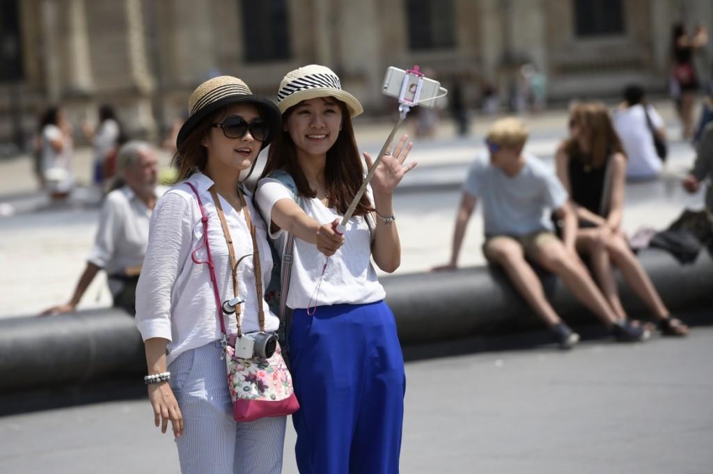 7779037486_des-touristes-prenant-un-selfie-a-cote-du-louvre-a-paris-le-2-juillet-2015